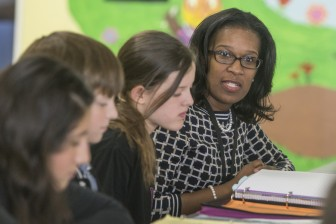 Principal Angela Watkins meeting with the Student Lighthouse Team in the lunch room as they go through their Data Binders where they keep track of their attendance, behavior, exercise programs, reading fluency and their weekly grades. Photo by Walt Stricklin